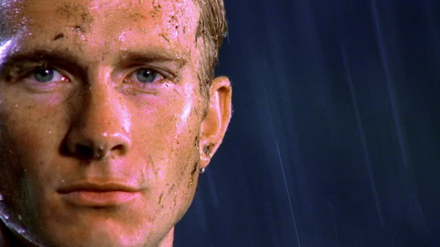 extreme close up muddy face of male soccer player standing in rain at night - dirty stock videos & royalty-free footage