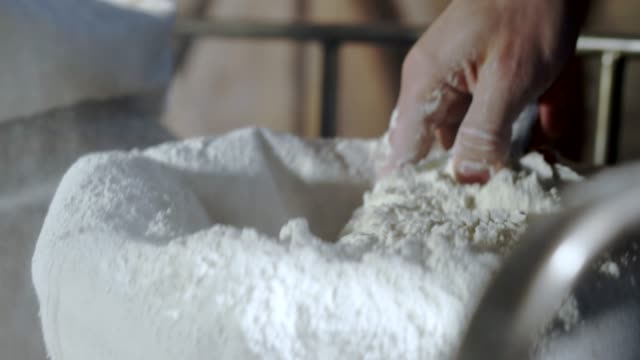 extreme close up of a baker's hand scooping flour from flour bags - manciata attività video stock e b–roll