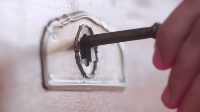 extreme close up of a hand unlocking an ancient coffer with a key. - open drawer stock videos & royalty-free footage