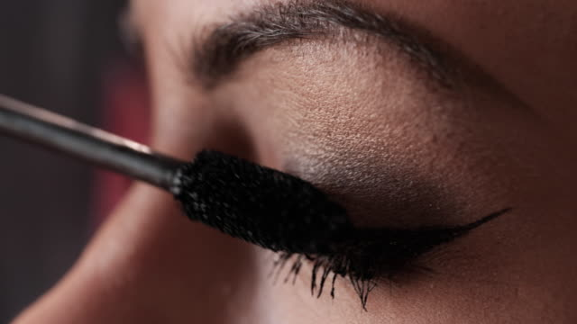 extreme close up of a woman applying mascara on eyelashes. - applying stock videos & royalty-free footage