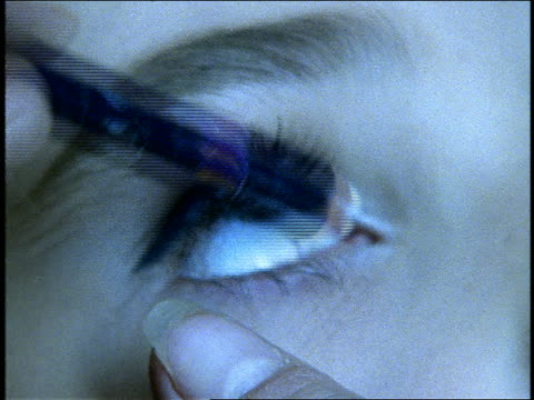 extreme close up of eyeliner being put on woman