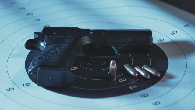 紙の盾の上に横たわっているグロック銃と弾丸組成の極端なクローズアップ - 全米ライフル協会点の映像素材/bロール