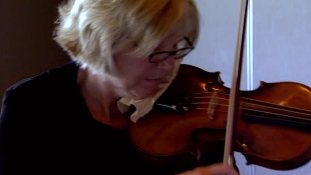 extreme close up of hand on violin and violin bow, handheld shot
