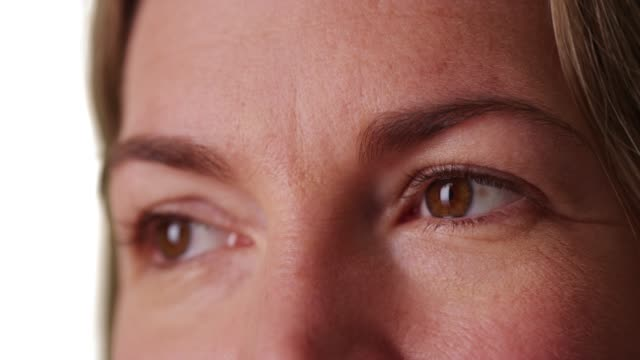 extreme close up of middle aged caucasian woman's eyes on white background - forehead stock videos and b-roll footage