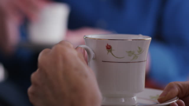 extreme close up of two coffee cups on a kitchen table; the hands of two men rest on the table and alternately pick up  the cup for an off-camera sip, then set it back down on a coaster. - cup bildbanksvideor och videomaterial från bakom kulisserna