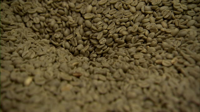 Extreme close up of white coffee beans moving through grinder.