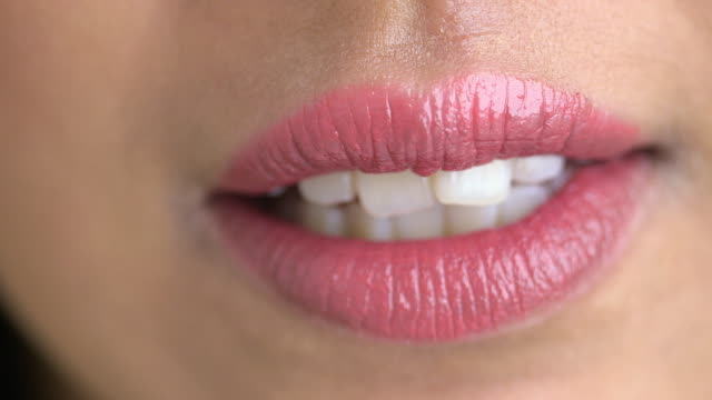 Extreme close up of woman biting her lower lip