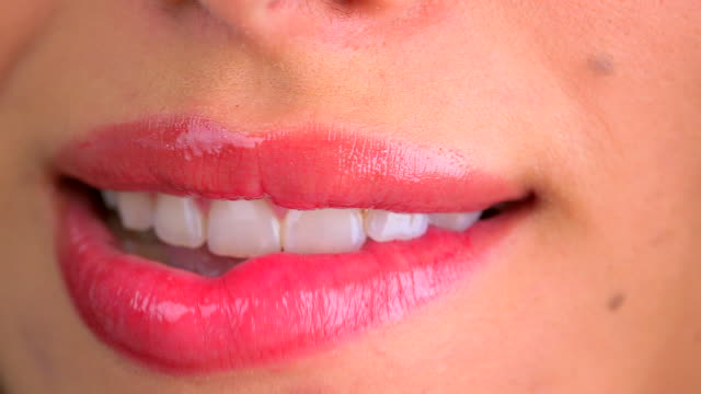 extreme close up of woman biting lower lip - lipgloss stock-videos und b-roll-filmmaterial
