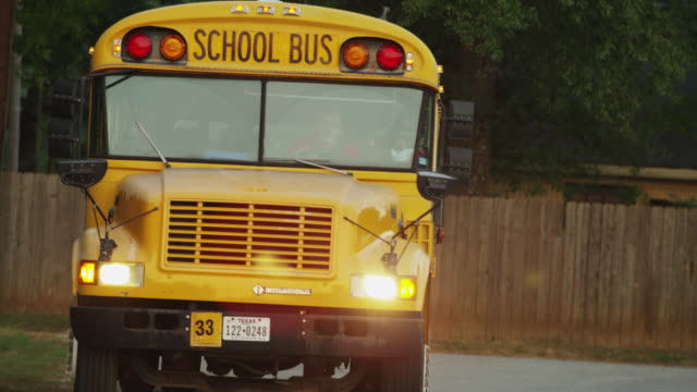 Extreme close up of yellow school bus turning in front of camera taking children to school early in the morning.