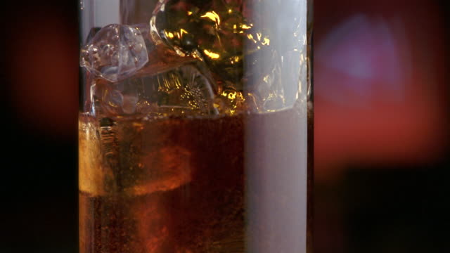 extreme close up pan cola being poured over alcohol and ice in glass / panama - carbonated drink stock videos & royalty-free footage