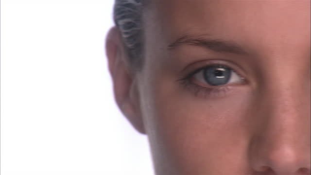 Extreme close up panning face of woman looking at camera / blinking