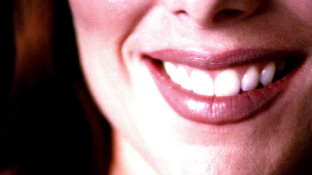 high contrast overexposed extreme close up portrait mouth of young woman smiling in studio - 歯点の映像素材/bロール