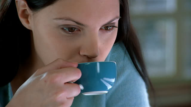 extreme close up portrait of woman drinking from coffee cup / looking at cam and smiling / brussels, belgium - tea cup stock videos & royalty-free footage