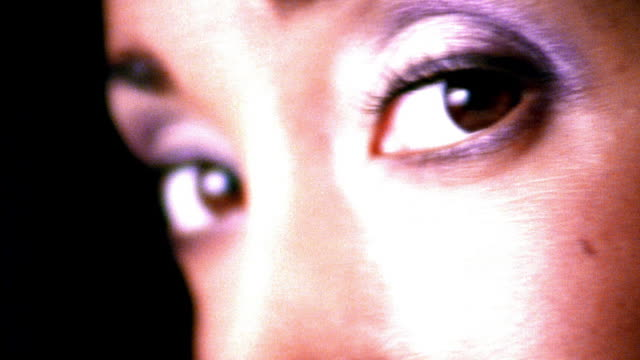 high contrast extreme close up rack focus brown eyes of young black woman turning to camera in studio - brown eyes stock videos & royalty-free footage