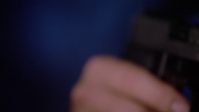 Extreme close up rack focus hand holding gun and shooting it at camera