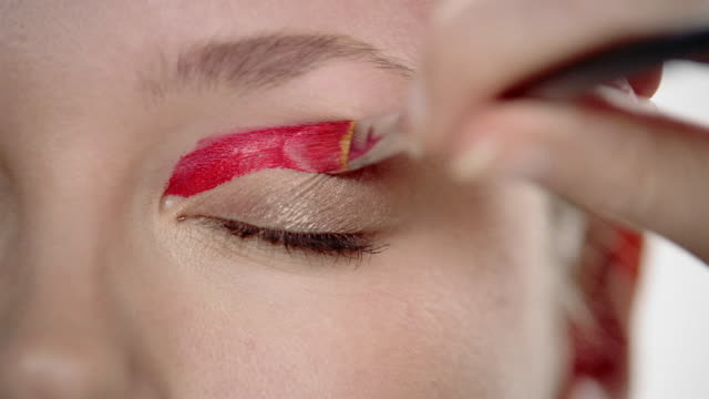 Extreme close up red cream eyeshadow being applied to woman's eyelid with brush / eye opening + looking at CAM