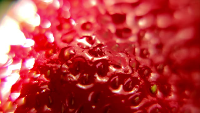 Extreme close up red strawberry slowly turning Abstract