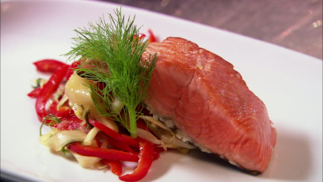 extreme close up salmon entre with garnish arranged on plate / being drizzled with oil / auckland, new zealand - plate stock videos & royalty-free footage