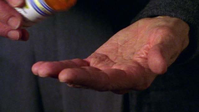 extreme close up senior man's right hand pouring pills from bottle into left hand
