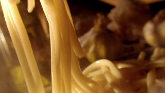 extreme close up strands of pasta falling on pile of pasta