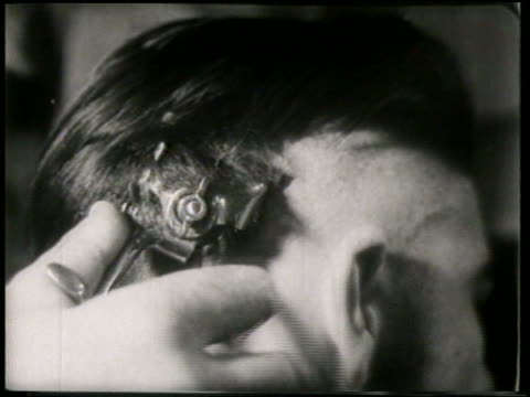 B/W 1951 extreme close up teen boy getting mohawk in barbershop / France / newsreel
