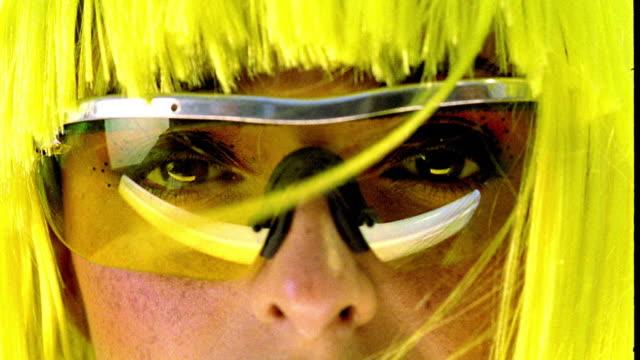 vídeos de stock, filmes e b-roll de yellow portrait extreme close up tilt down woman with fluorescent yellow hair + sunglasses looking into camera - superexposto