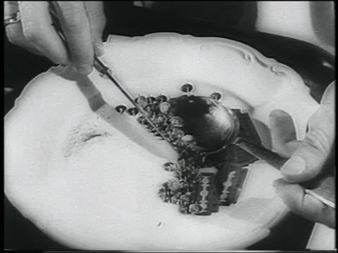 b/w extreme close up tilt up man spooning up tacks + razor blades + eating them - 画鋲点の映像素材/bロール