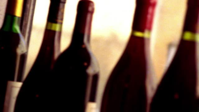 vidéos et rushes de extreme close up tilt up pan rack focus wine bottles in window of store / provence, france - bouteille de vin