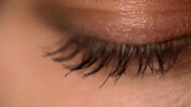 vidéos et rushes de extreme close up tilt up pan woman's blue eye opening - oeil humain