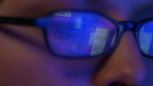 extreme close up tilt up woman's face with spreadsheet on computer screen reflecting in eyeglasses - number stock videos & royalty-free footage