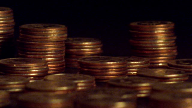 vídeos de stock, filmes e b-roll de extreme close up time lapse stacks of coins magically increasing in size - moeda