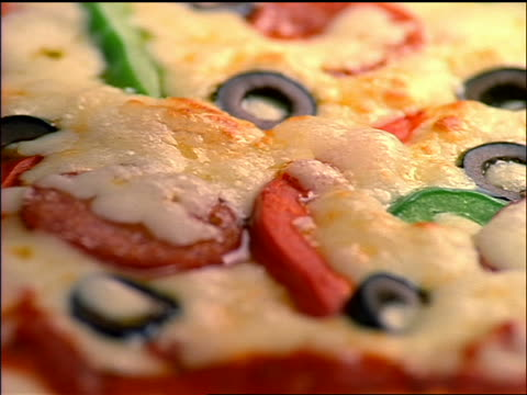 extreme close up top of pizza with bubbling cheese