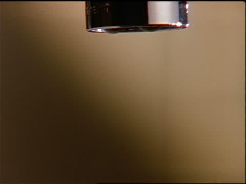 vídeos de stock, filmes e b-roll de extreme close up water faucet dripping - enfoque de objeto sobre a mesa