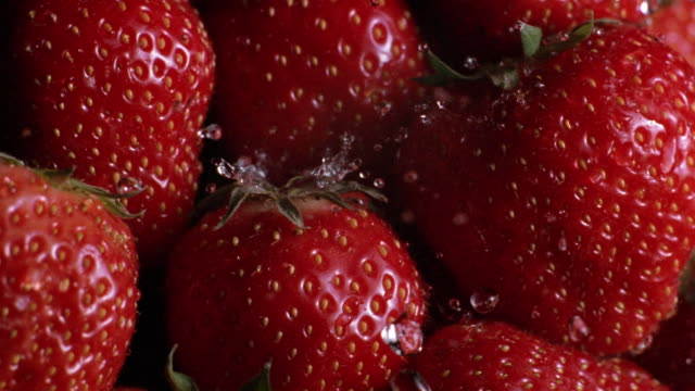 Extreme close up water sprinking pile of strawberries
