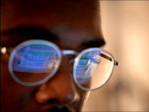 extreme close up webcrawler display reflected in eyeglasses of black man - spegling bildbanksvideor och videomaterial från bakom kulisserna