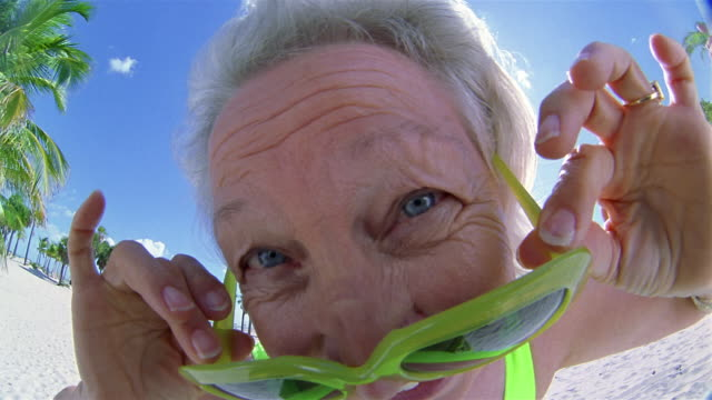 Extreme close up woman pulling down sunglasses and looking at CAM