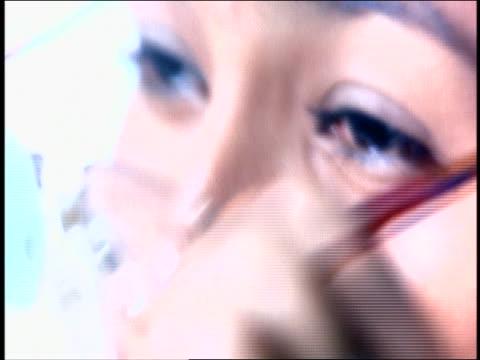 extreme close up woman taking off eyeglasses + rubbing eyes