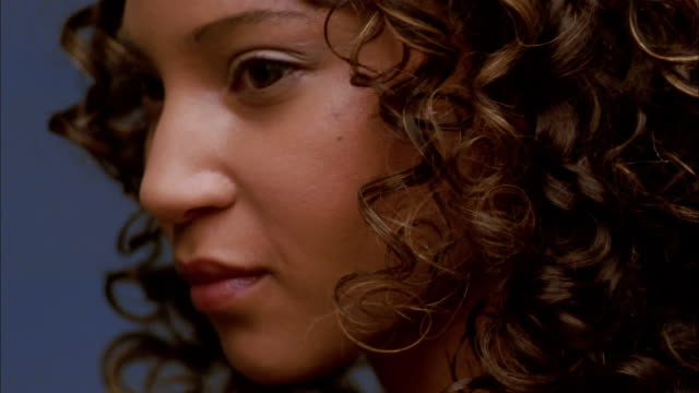 extreme close up woman w/curly hair turning and smiling - profile stock-videos und b-roll-filmmaterial