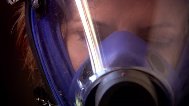 vidéos et rushes de extreme close up woman wearing gas mask - respirer