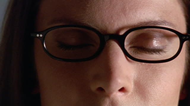 Extreme close up woman wearing glasses, face half in shadow / opening her eyes
