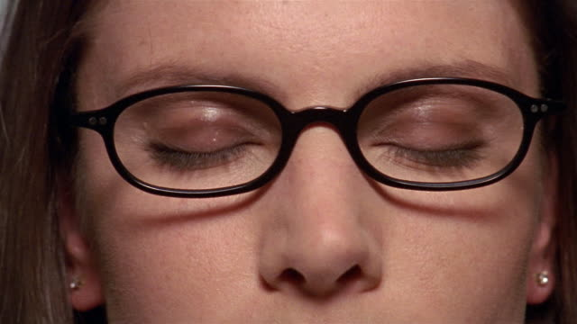 Extreme close up woman wearing glasses opening her eyes