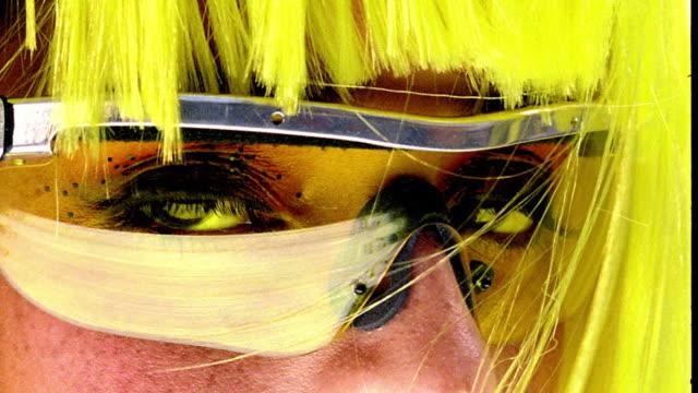 vídeos de stock, filmes e b-roll de yellow portrait extreme close up woman with fluorescent yellow hair + sunglasses looking into camera - superexposto