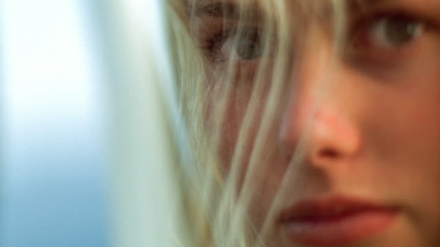 Extreme close up woman with long blonde hair blowing in wind
