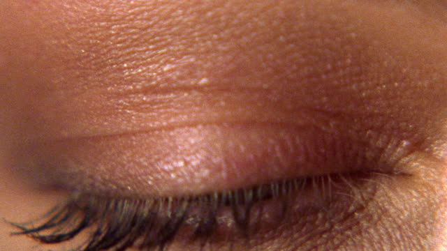extreme close up woman's blue eye opening