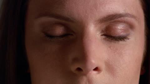 vídeos y material grabado en eventos de stock de extreme close up woman's face, half in shadow / opening her eyes - ojos cerrados