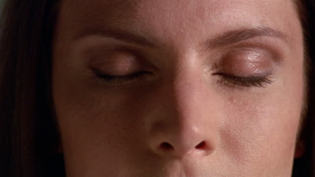 Extreme close up woman's face, half in shadow / opening her eyes