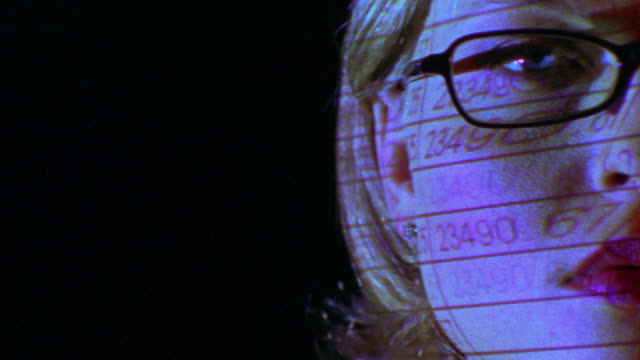 extreme close up PAN woman's face in eyeglasses with spreadsheet reflections from computer screen