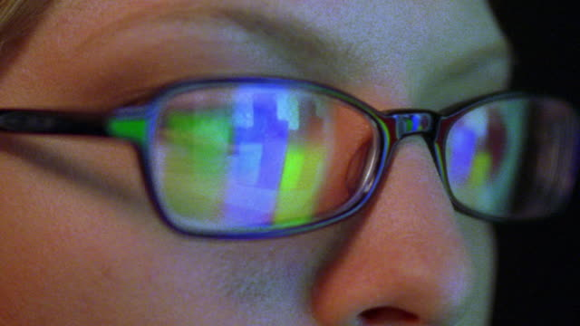 extreme close up woman's face with changing computer screen reflecting in eyeglasses - spectacles stock videos & royalty-free footage