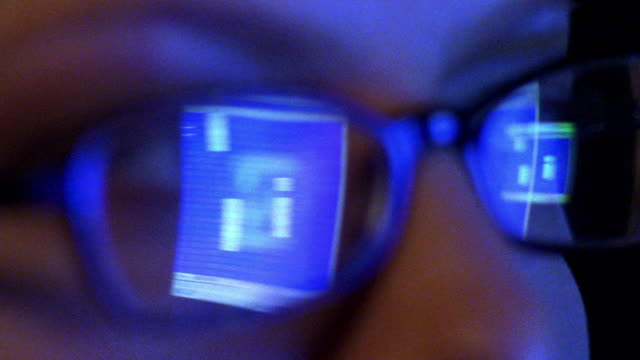 extreme close up woman's face with spreadsheet on computer screen reflecting in eyeglasses