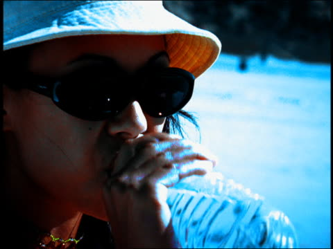 stockvideo's en b-roll-footage met extreme close up young woman drinking water from bottle outdoors / venice beach, los angeles, california - hoog contrast